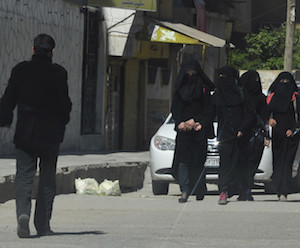 Female school students wearing a full veil (niqab) walk along a street in the northern province of Raqqa